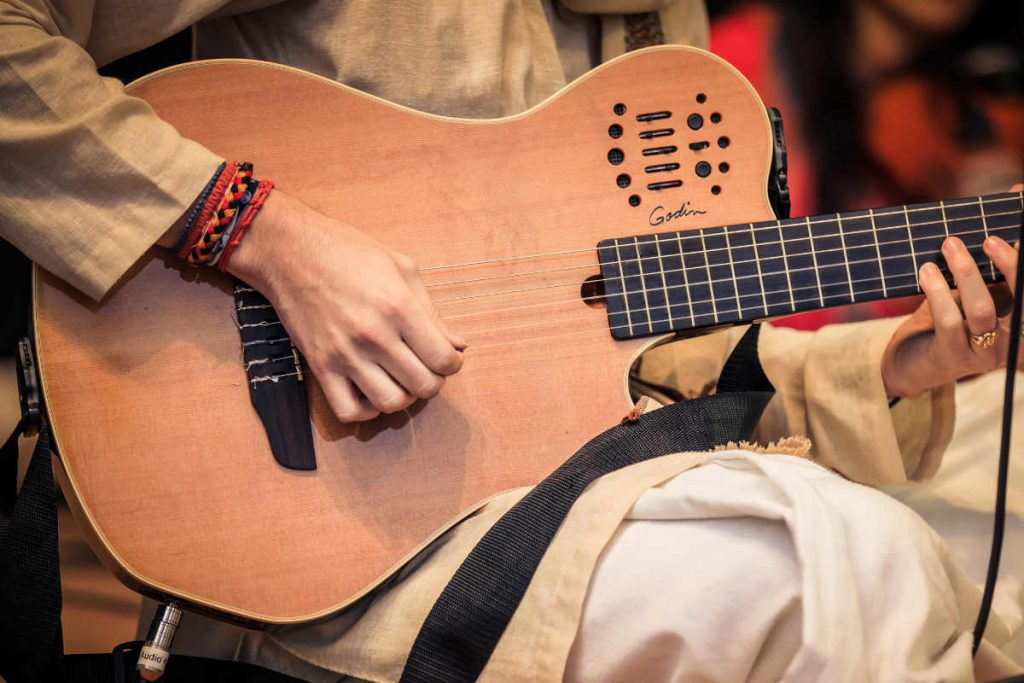 Guitar being played at Kirtan event